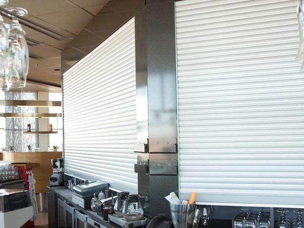 Avskiljningsjalusi Macro HK monterad i spritskåp på bar/restaurang