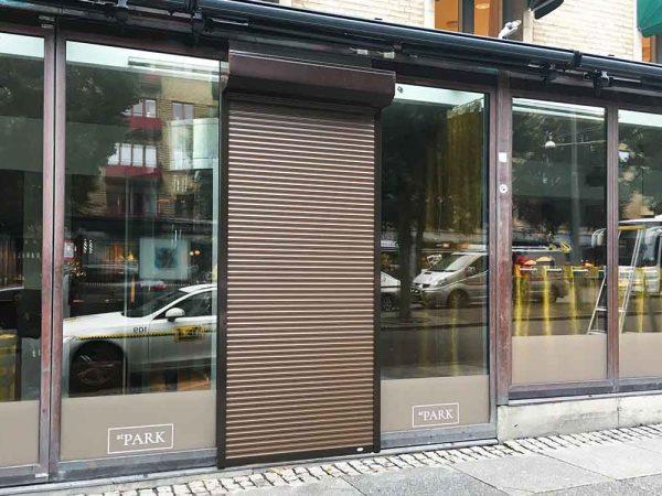 Skyddsjalusi Mini Safe Aluminum, brun standard, framför exklusiv restaurang